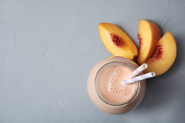 peach protein shake next to peaches