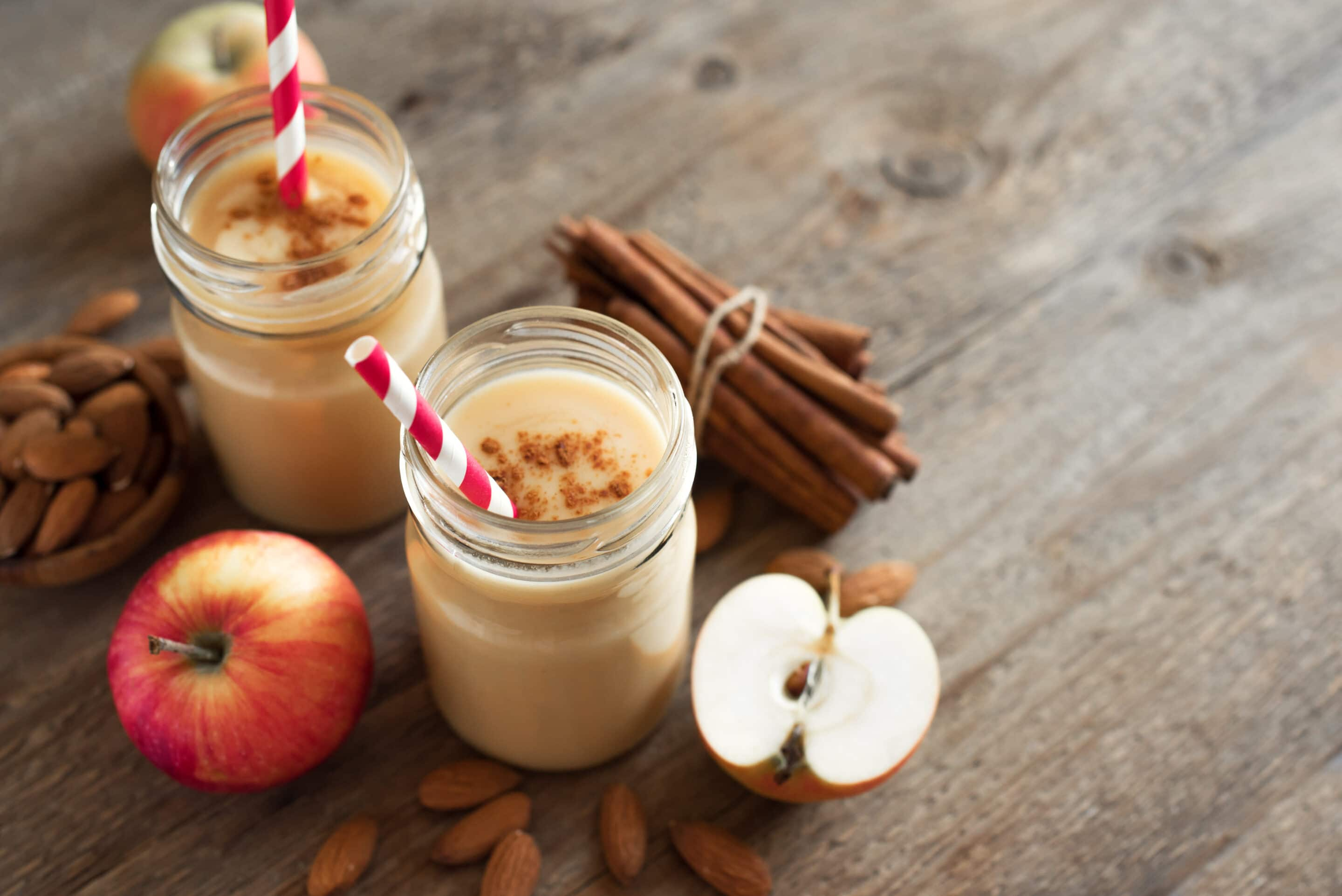 apple pie protein shake in glasses next to apples and cinnamon
